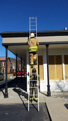 Firefighters on a ladder getting a check.
